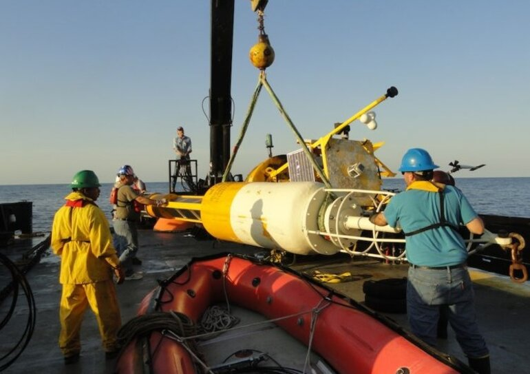 Workers prepare a buoy to be launched into the gulf.