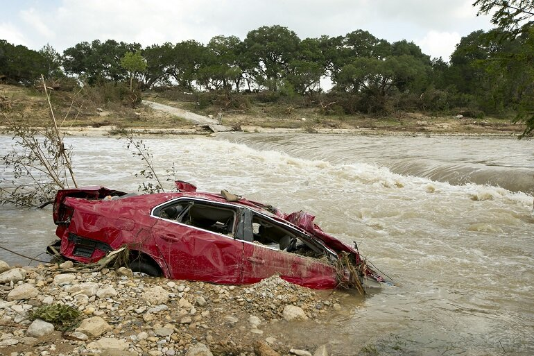 Destroyed car is submerged in the Blanco River