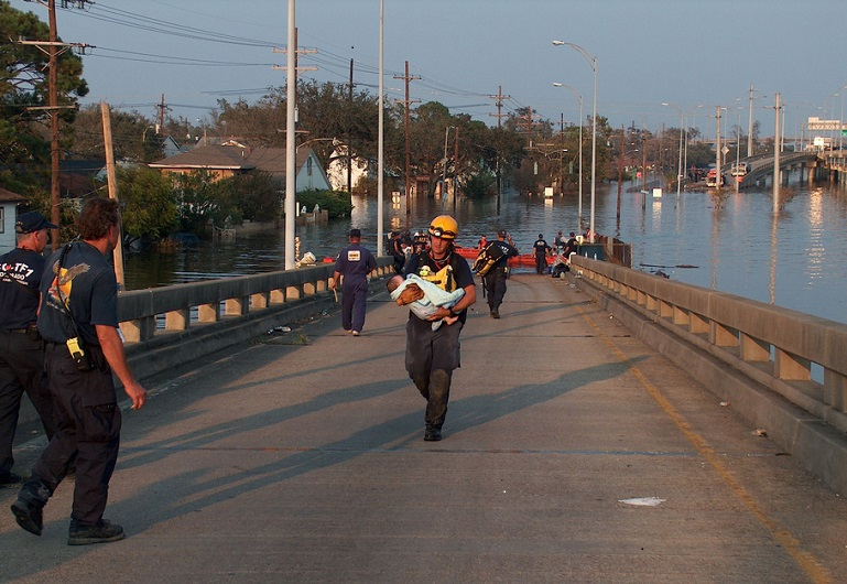 A hazmat technician carries an infant to safety in New Orleans